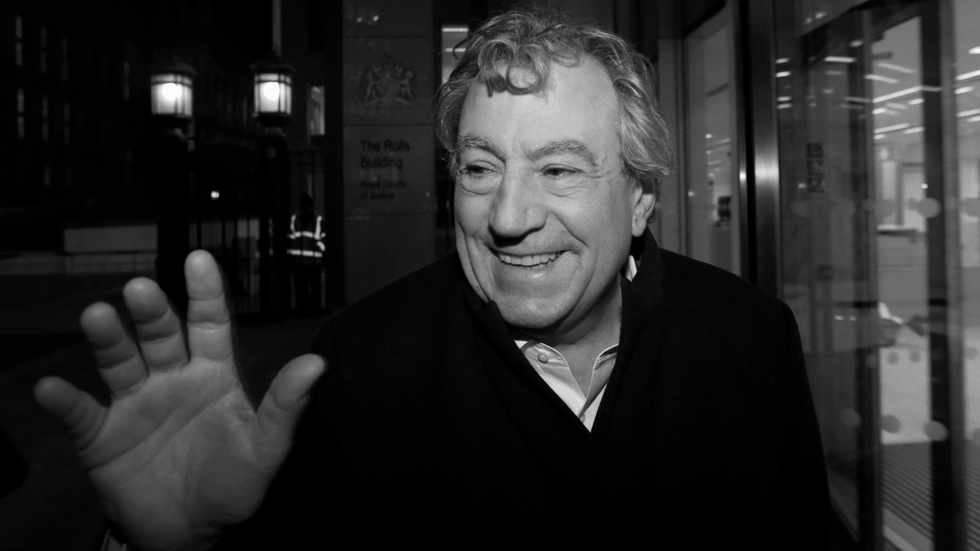 FILE PHOTO: British comedian Terry Jones smiles as he leaves The Rolls Building in central London November 30, 2012. Three members of the Monty Python British comedy troupe were in court in London on Friday for the opening of a lawsuit over the profi