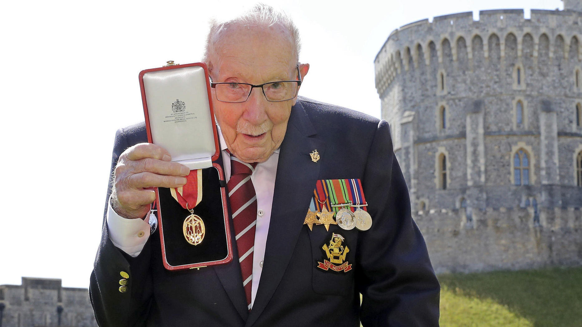 FILE - In this Friday, July 17, 2020 file photo, Captain Sir Thomas Moore poses for the media after receiving his knighthood from Britain's Queen Elizabeth, during a ceremony at Windsor Castle in Windsor, England. Tom Moore, the 100-year-old World Wa