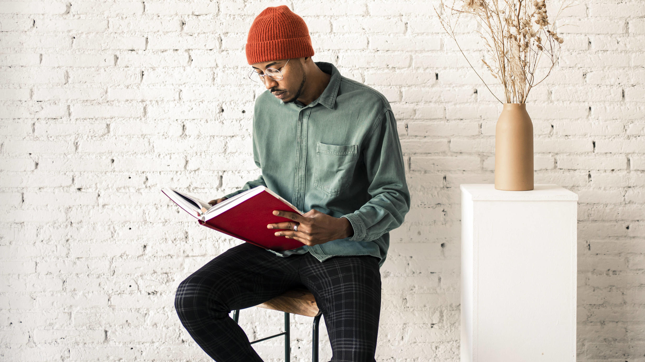 Man in knit hat reading book by dried plant vase against white brick wall model released Symbolfoto property released RCPF00507
