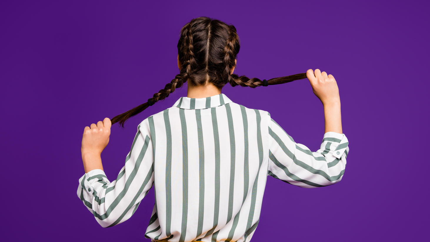Rear behind view photo of beautiful pretty lady holding braids hands, hiding face shy person wear striped shirt yellow trousers isolated purple color background (Rear behind view photo of beautiful pretty lady holding braids hands, hiding face shy pe