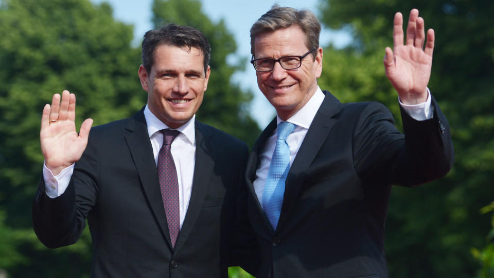 CORRECTING THE PHOTOGRAPHERS NAME-German Foreign Minister Guido Westerwelle (R) and his partner Michael Mronz pose upon arrival for a state dinner for the US president in Berlin, on June 19, 2013. US President Barack Obama walks in John F. Kennedy's