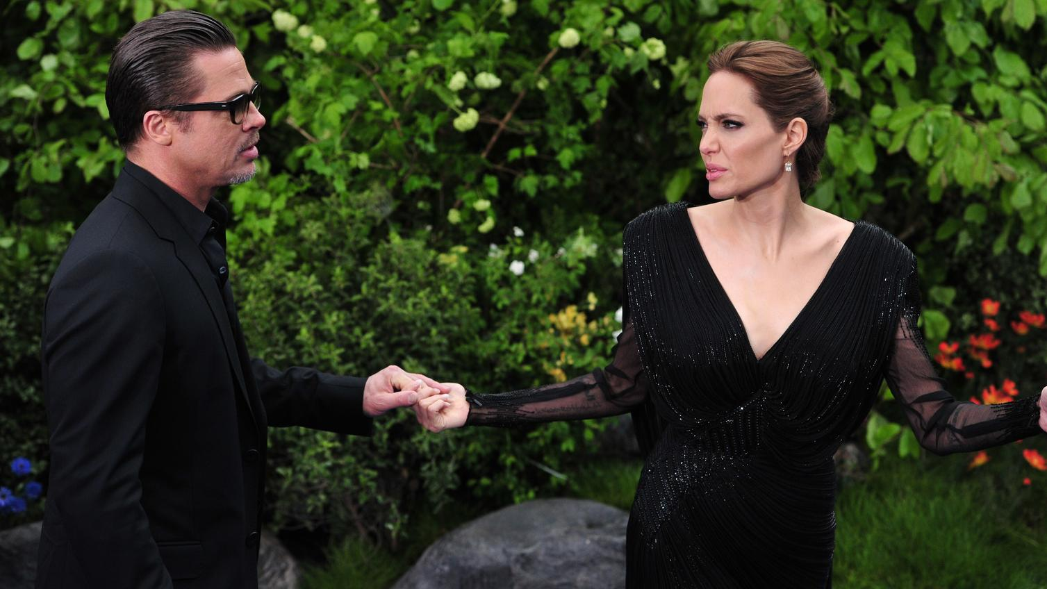 "US actress Angelina Jolie (R) speaks with her husband US actor Brad Pitt as they arrive for the premiere of the film ""Maleficent"" at Kensington Palace in London on May 8, 2014.  AFP PHOTO/CARL COURT        (Photo credit should read CARL COURT/AFP/Get"