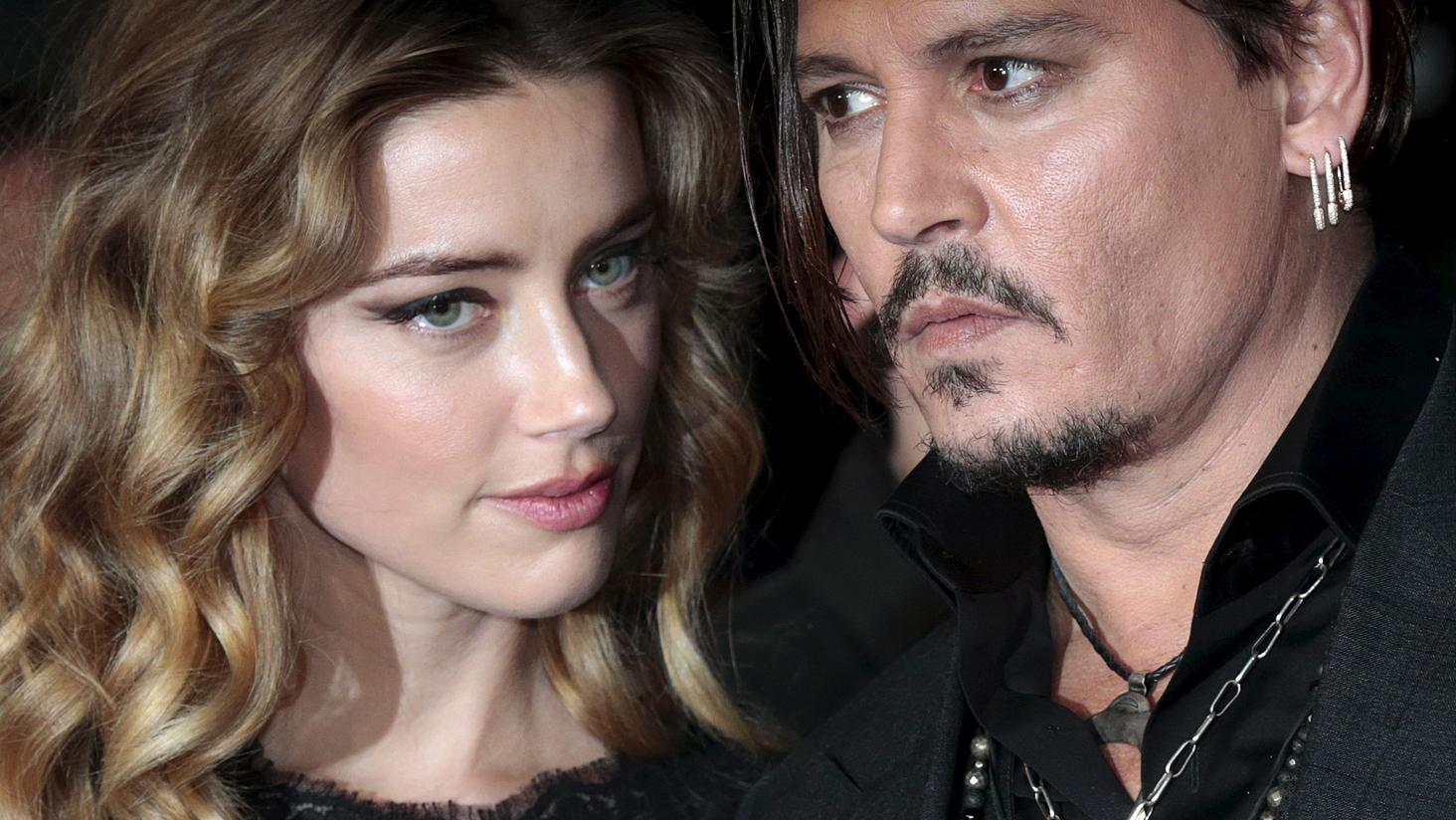 "Cast member Johnny Depp and his actress wife Amber Heard arrive for the British premiere of the film ""Black Mass"" in London, Britain October 11, 2015. REUTERS/Suzanne Plunkett/File Photo"