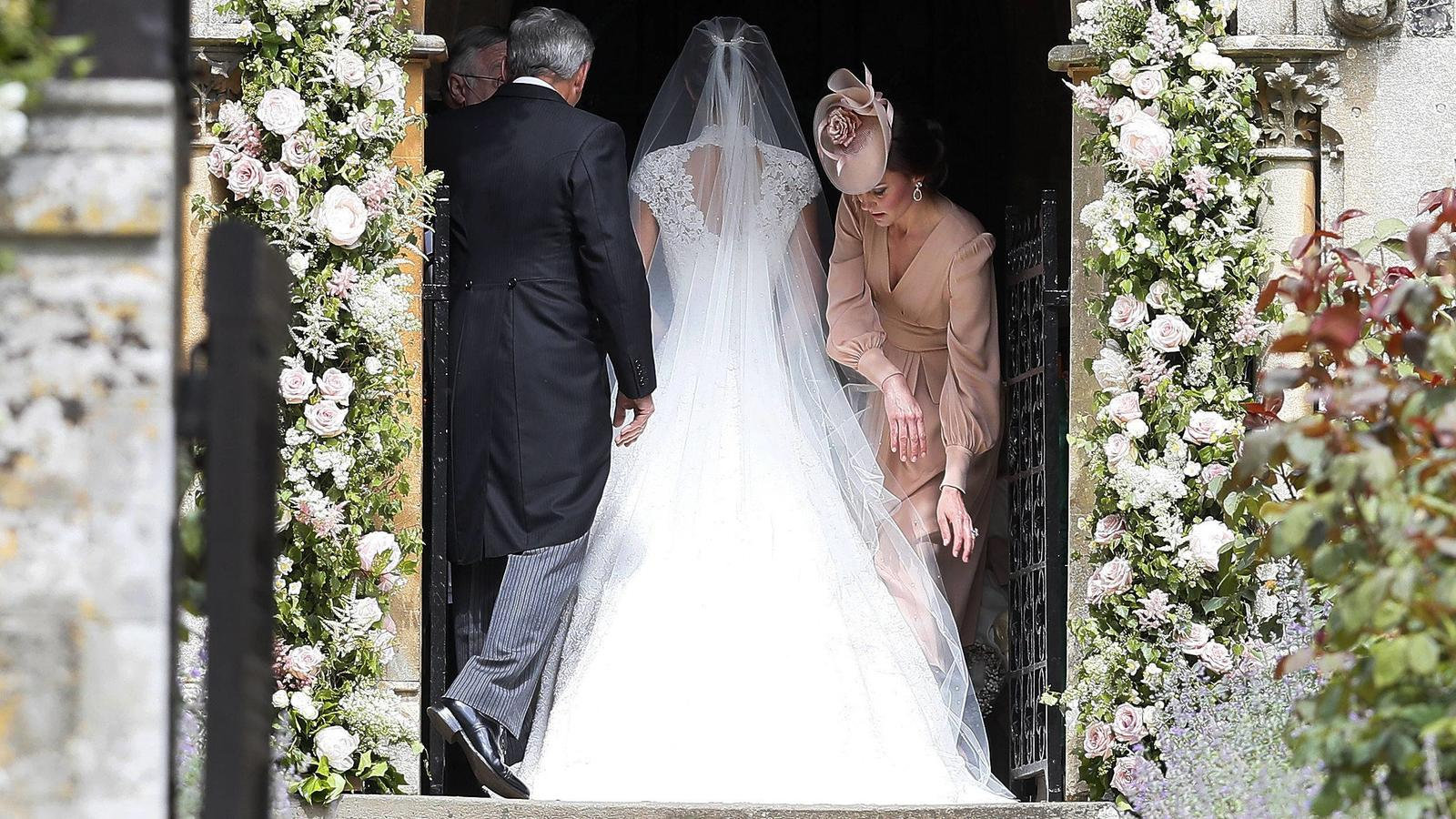 The Duchess of Cambridge, (right) , arranges the train of her sister Pippa Middleton as she arrives, at St Mark s church in Englefield, Berkshire, for her wedding to her millionaire groom James Matthews at an event dubbed the society wedding of the y