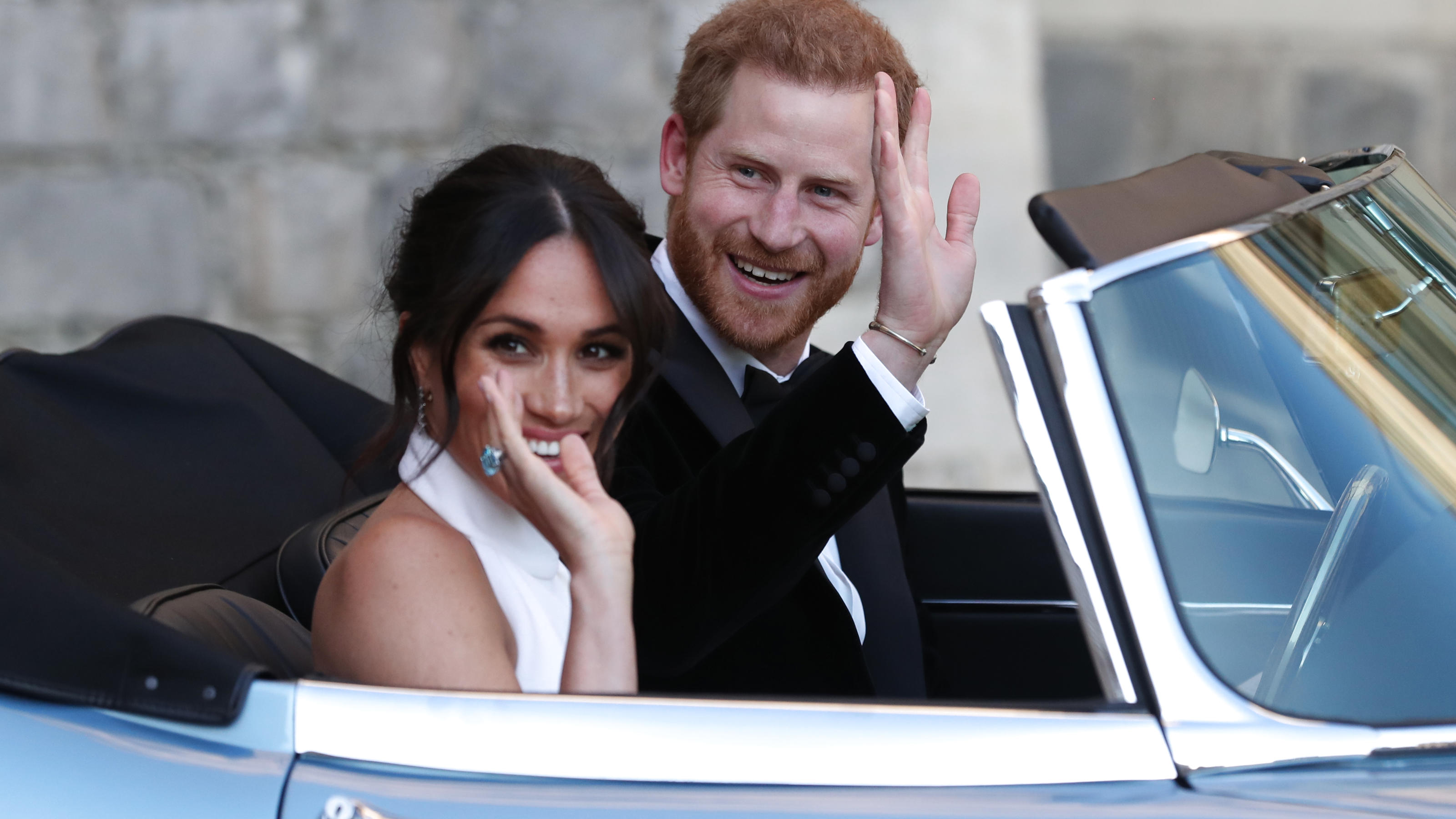 WINDSOR, UNITED KINGDOM - MAY 19: Duchess of Sussex and Prince Harry, Duke of Sussex wave as they leave Windsor Castle after their wedding to attend an evening reception at Frogmore House, hosted by the Prince of Wales on May 19, 2018 in Windsor, Eng
